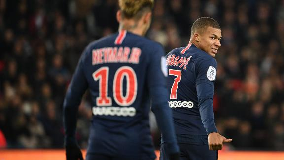 Mbappe gestures and smiles towards Neymar during a Ligue 1 match.