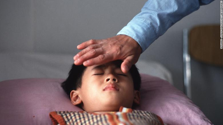Qi gong master Liang Jian Sheng treats a short-sighted patient by transferring his energy to the young boy at a hospital in Guangzhou.