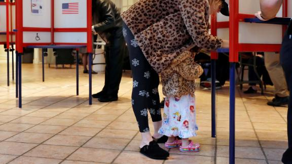 Falcon Wien, 2, huddles under the coat of her mother, Sarah, as she votes in Mount Kisco, New York.