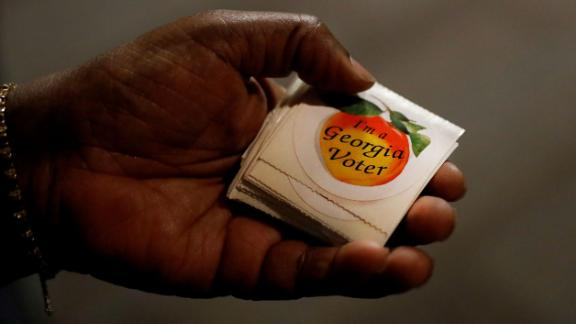 A poll worker hands out stickers in Atlanta.