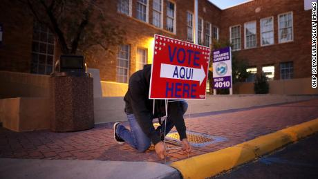 Volunteer Albert Lopez, 18, sets  up signs directing voters to a polling place at El Paso Community College-Rio Grande Campus before dawn on Election Day.