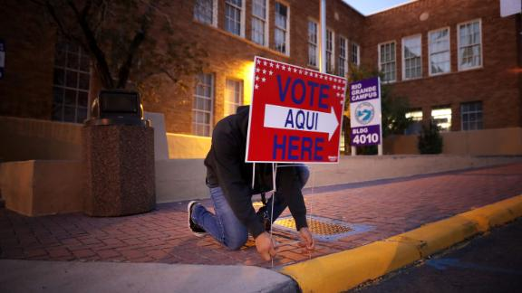 Volunteer Albert Lopez sets out signs directing voters to a polling place in El Paso, Texas.