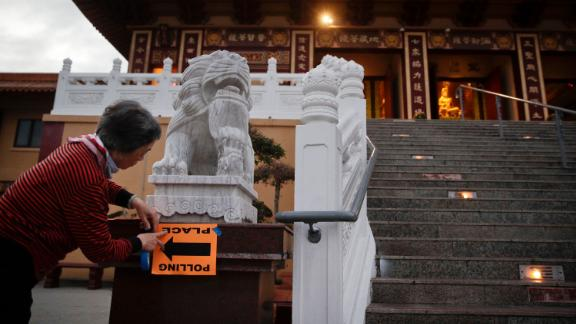 Volunteer Fu Hua Chen puts up a sign near a polling place at the Hsi Lai Temple in Hacienda Heights, California.