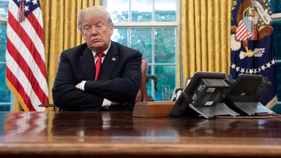 US President Donald Trump sits at the Resolute Desk during a briefing on Hurricane Michael in the Oval Office of the White House in Washington, DC, October 10, 2018. (Photo by SAUL LOEB / AFP)        (Photo credit should read SAUL LOEB/AFP/Getty Images)