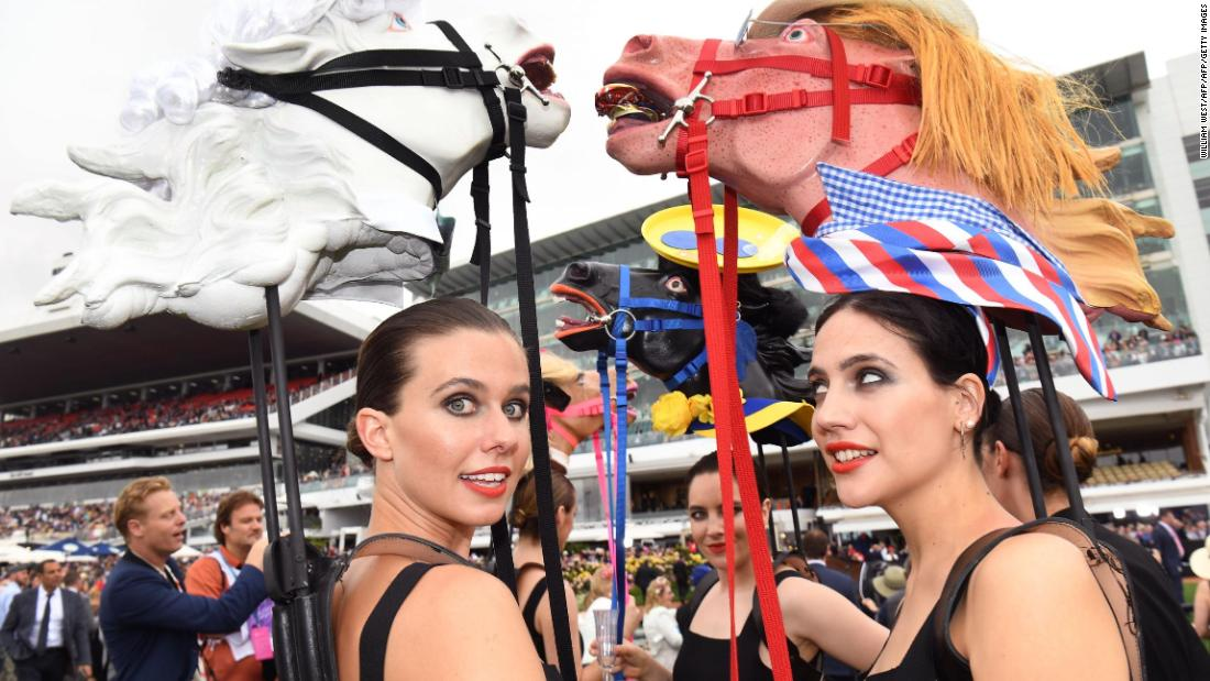 Heavy rain did nothing to dampen the spirit of race-goers, some of whom wore figures of horse heads ahead of the running of the Melbourne Cup.