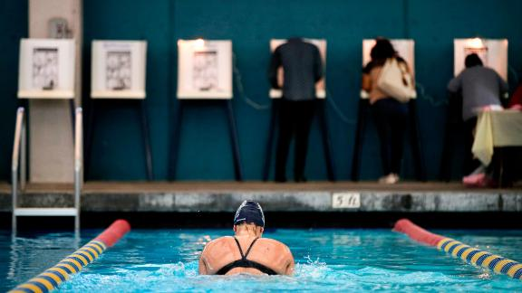Sarah Salem swims at the Echo Deep Pool in Los Angeles as voters cast their ballots nearby.