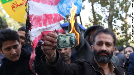 An Iranian protester burns a dollar bill during a demonstration outside the former US embassy in the Iranian capital of Tehran on November 4, 2018.