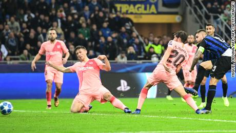 Mauro Icardi (R) of Inter Milan scores against Barcelona.