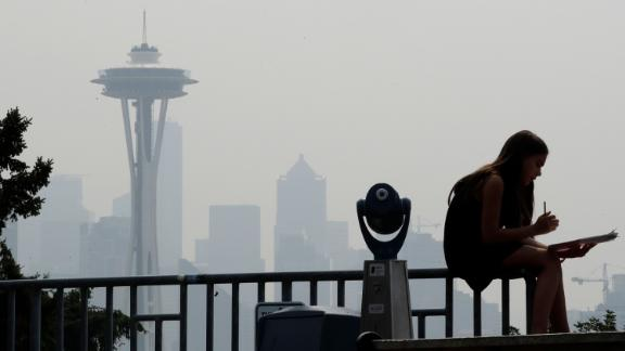 File - In this Aug. 14, 2018 file photo, a girl works on a drawing next to an unused viewing scope as a smoky haze obscures the Space Needle and downtown Seattle behind. Alarmed by as much as $20 million in lost tourism revenue in July due to visitors' fear of wildfires, California tourism officials are teaming up with Oregon and Washington to reassure tourists they're safe to visit after deadly wildfires that have burned homes and clogged the air. (AP Photo/Elaine Thompson, File)