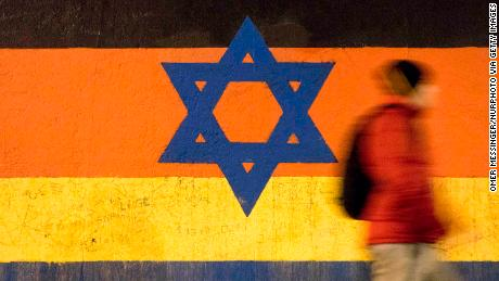 A man passes by a section of the Berlin Wall with a graffiti featuring the Star of David and the Israeli flag with the German flag, by the artist  by Guenther Schaefer. East Side Gallery, Berlin.***ISRAEL OUT*** (Photo by Omer Messinger/NurPhoto via Getty Images)