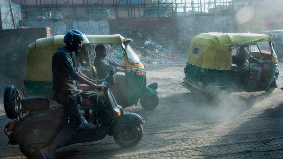 Auto rickshaw drivers pass a building site in Old Delhi.