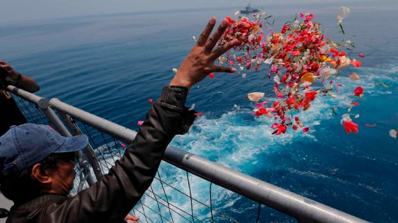 A relative of one of the crash victims tosses flower petals from an Indonesian Navy ship on Tuesday, November 6.