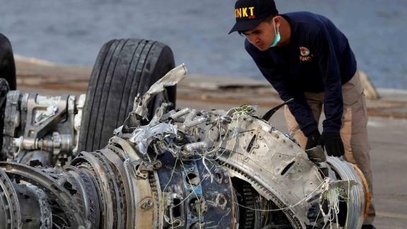 An Indonesian official examines a turbine engine from the plane on Sunday, November 4.
