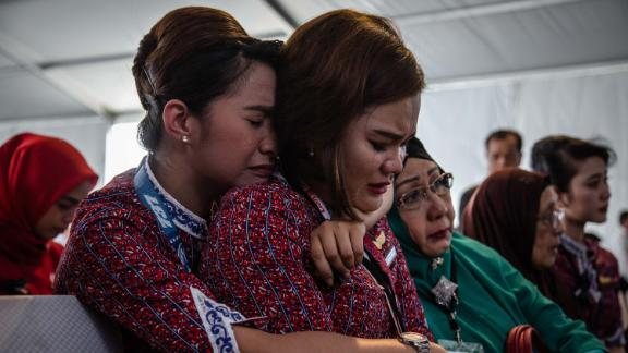 Victims' families and colleagues react on a Navy ship as they're ferried to the crash site on November 6.