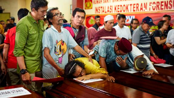 People in Jakarta grieve over the coffin of a relative on November 4.