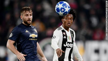 Luke Shaw (L) Juan Cuadrado prepare to compete for the ball.