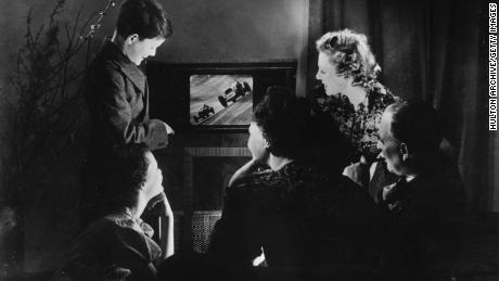 circa 1938:  A family watch motor racing on their new television set.  (Photo by Hulton Archive/Getty Images)