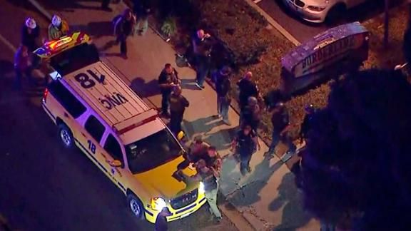 Officers stand near a police SUV at the shooting scene in an image from aerial video.