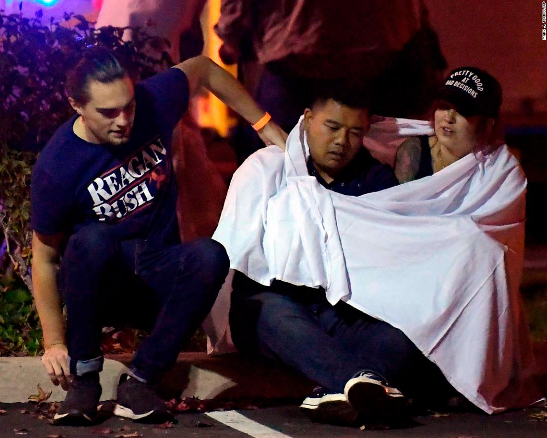 People comfort each other near the shooting scene.