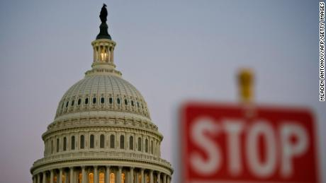 A stop sign is seen at dusk next to the US Capitol building on September 30, 2013. AFP PHOTO/ MLADEN ANTONOV / Getty Images