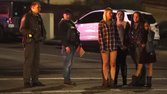 Women who fled from the shooting stand by a sheriff's deputy.