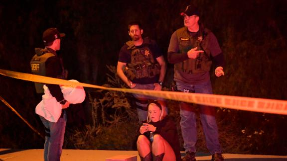"""Sheriff's deputies speak to a potential witness as they stand near the scene Thursday, Nov. 8, 2018, in Thousand Oaks, Calif. where a gunman opened fire Wednesday inside a country dance bar crowded with hundreds of people on """"college night,"""" wounding 11 people including a deputy who rushed to the scene. Ventura County sheriff's spokesman says gunman is dead inside the bar. (AP Photo/Mark J. Terrill)"""