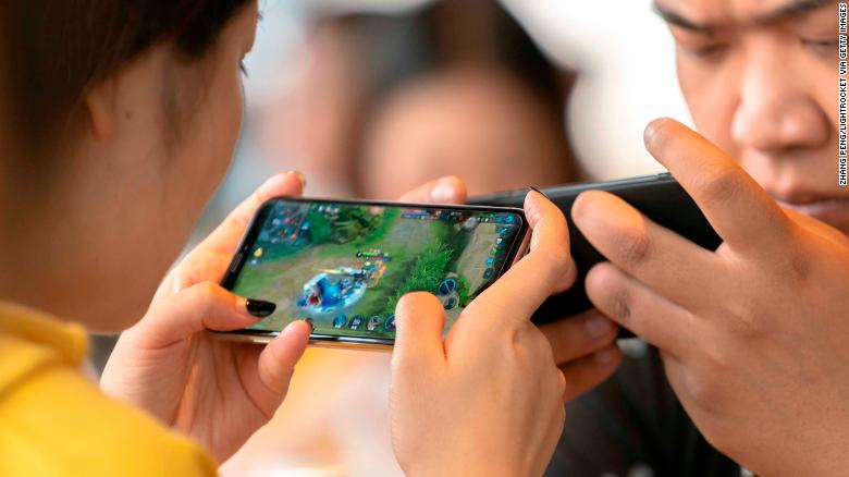 Young people play video games on mobile phones in a cafe.