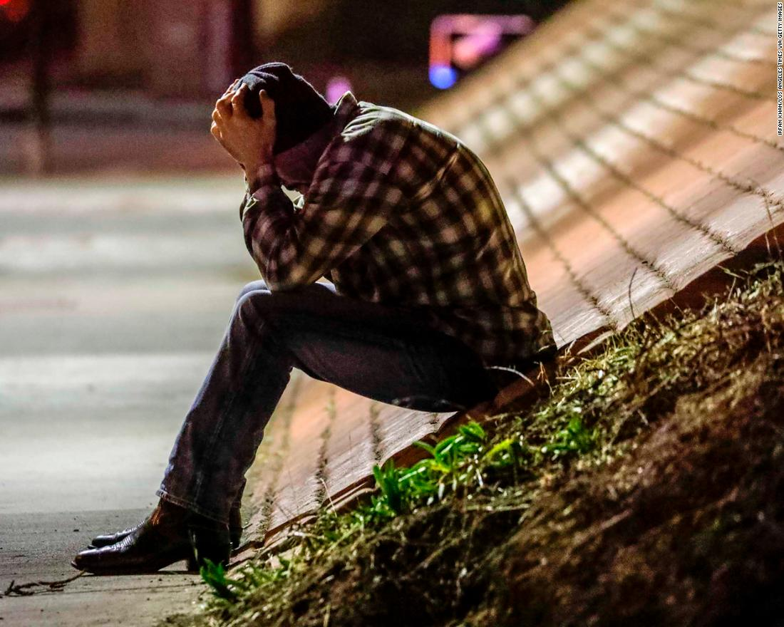 Tim Dominguez, who was in the bar with his son, sits distraught under a freeway overpass near the crime scene in Thousand Oaks.