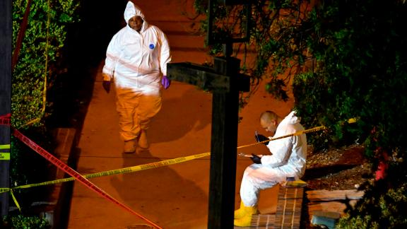 A forensics team collects evidence at the scene.