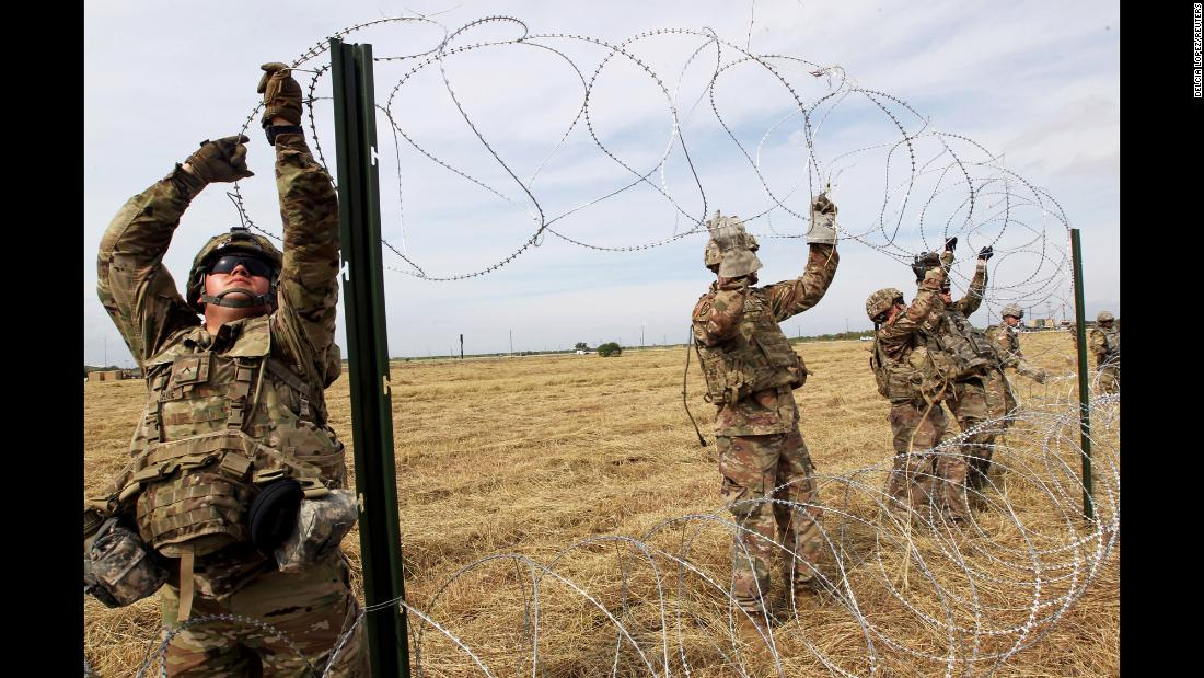 "US Army soldiers from Fort Riley, Kansas, put up razor-wire fence Sunday, November 4, for an encampment to be used by the military near the US-Mexico border in Donna, Texas. Just before the midterm elections, President Donald Trump <a href=""https://www.cnn.com/2018/10/29/politics/pentagon-border-troops-migrants/index.html"" target=""_blank"">ordered thousands of troops to the southern border </a>to guard against what he has called an ""invasion"" by a group of migrants heading north through Mexico to the United States."