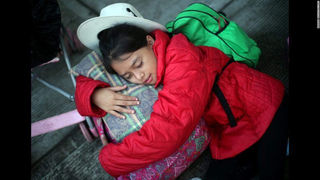 "Nancy Alejandra, an 11-year-old migrant from Honduras <a href=""https://www.cnn.com/2018/11/04/americas/migrant-theories-experts-midterms/index.html"" target=""_blank"">heading to the United States,</a> sleeps on the side of the road in Cordoba, Mexico, on Monday, November 5. She was waiting to board a bus to Mexico City."