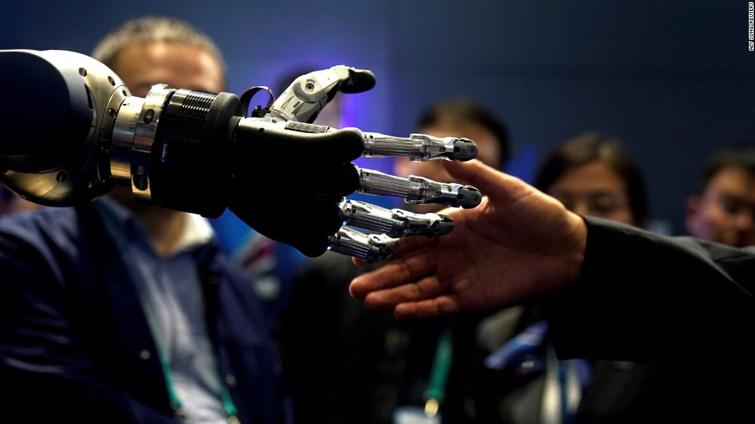 A man in Shanghai, China, tries to shake hands with a anthropomorphic gripper hand during the China International Import Expo on Tuesday, November 6.