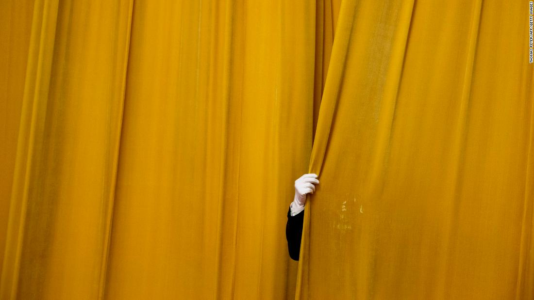 A security official in Beijing closes a curtain at the Great Hall of the People before Chinese President Xi Jinping met with former US Secretary of State Henry Kissinger on Thursday, November 8.