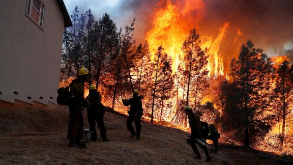 A group of US Forest Service firefighters monitor a back fire while battling to save homes from the Camp Fire in Paradise, California, on November 8.