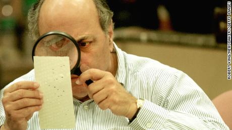 Judge Robert Rosenberg uses a magnifying glass to examine a punch card ballot on November 24, 2000 during a vote recount in Fort Lauderdale, Florida.  The close 2000 race led to a recount in some counties in Florida.