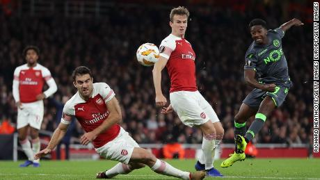 Sporting Lisbon's Abdoulay Diaby is blocked by Sokratis Papastathopoulos and Rob Holding of Arsenal during the two teams' Europa League group match in London.