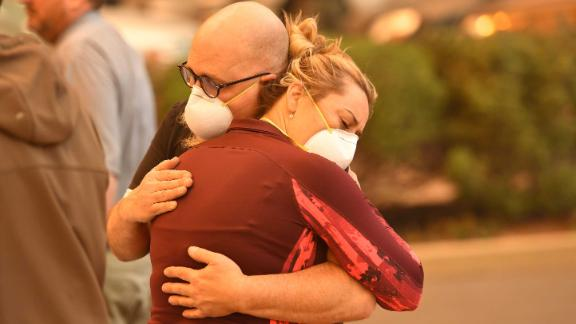 People embrace in the parking lot of a Paradise hospital as the Camp Fire engulfed it on November 8.