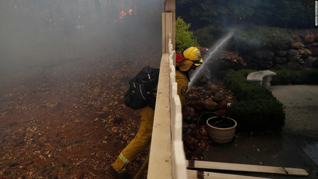 A firefighter works to extinguish a spot fire at a home in Paradise.
