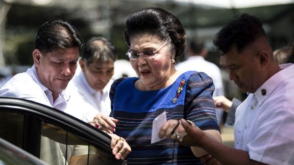 Imelda Marcos is assisted to her car after visiting her husband's tomb, August 28, 2017.