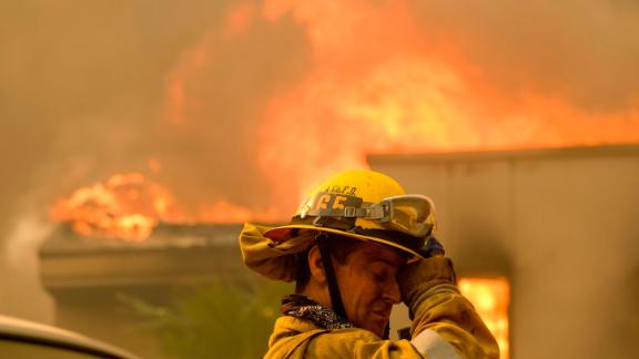 A firefighter keeps watch as the Woolsey Fire burns a home near Malibu Lake on November 9.