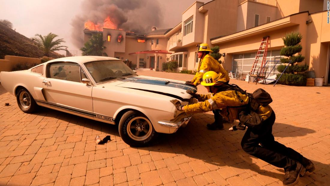 Firefighters push a vehicle from a garage as the Woolsey Fire burns a home in Malibu on November 9.