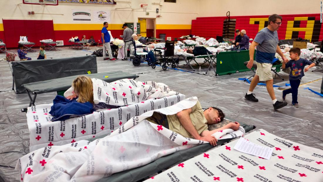 Evacuees rest on cots supplied by the Red Cross at a Los Angeles high school gym on November 9.