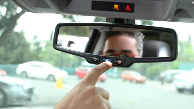 A man presses the blue OnStar button in a GM car.