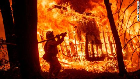 Firefighter Jose Corona sprays water as flames consume a house in Magalia, California.
