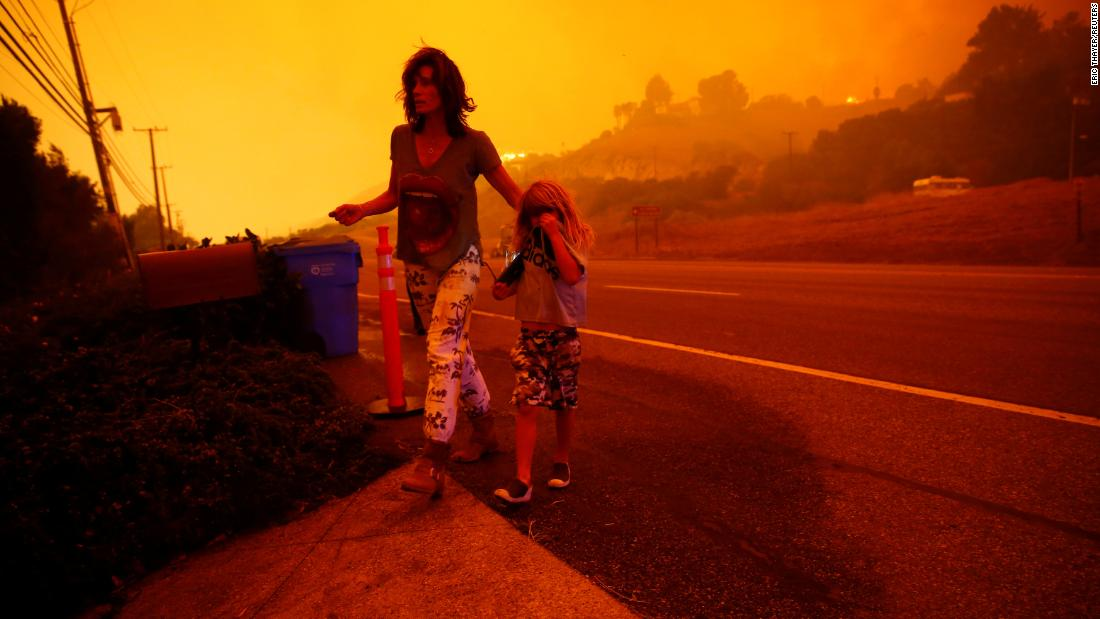Gabi and Jonah Frank walk on the Pacific Coast Highway as the Woolsey Fire threatens their Malibu home on Friday.