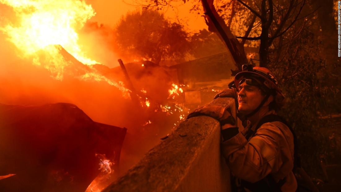 Malibu Mayor Rick Mullen, who is also a firefighter, surveys a house engulfed in flames in his city as the Woolsey Fire comes down a hill on November 9.
