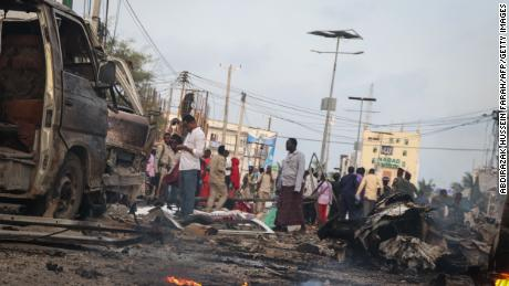 People gather in the street amid wreckage from car bombings in Mogadishu, Somalia.