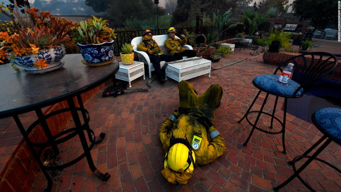 Firefighters Omar Velasquez, center, Cory Darrigo, left, and Sam Quan rest in the backyard of a home in Westlake Village on November 9 after fighting the Woolsey Fire all night.