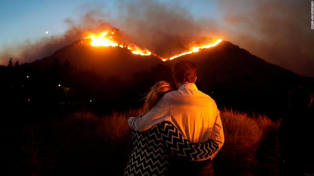 Roger Bloxberg and his wife, Anne, hug as they watch a wildfire on a hilltop Friday, November 9, near their home in the West Hills area of Los Angeles.