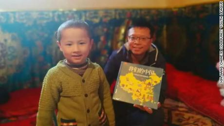 "A civilian worker presents a Uyghur child whom he has been assigned to treat as his ""relative"" with a picture book titled Our China, in an undated photo from Xinjiang's Chinese Communist Youth League."